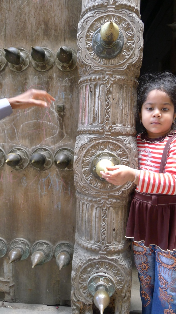 This little girl is too cute and she happened to be grasping an impressively designed door.